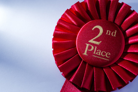 Segundo lugar ganadores roseta en cinta roja plisada con letras de oro que se otorgará al segundo participante colocado en una competición, con copyspace