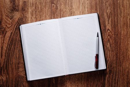 open diary: Close up Ballpoint Pen on Blank Open Notebook Placed on Wooden Table. Emphasizing Copy Space at the Center. Stock Photo