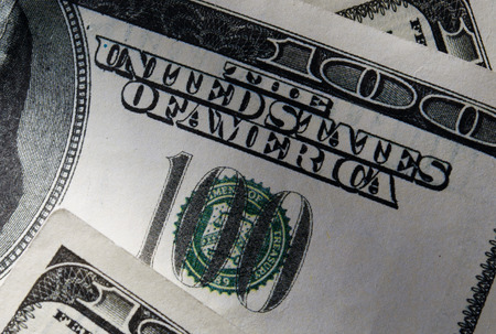 emphasizing: Close up US Dollar Bills, Emphasizing 100 and The United States of America Texts.