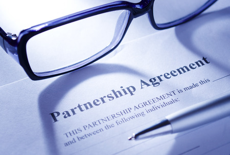 Contract Concept - Conceptual Close up of Eyeglasses and Ballpoint Pen on Top of Partnership Agreement Paper Placed on White Table. photo