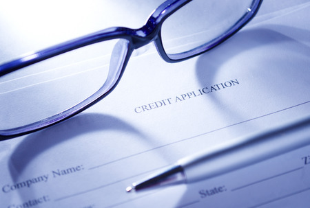 business credit application: Conceptual Close up of Unisex Eyeglasses and Ballpoint Pen on Top of Blank Credit Application Form Paper.