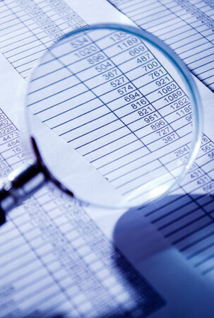 emphasizing: Conceptual Magnifying Glass on Top of Sales Invoice Reports, Emphasizing Scrutinizing Figures.