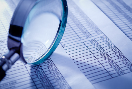 Conceptual Magnifying Glass on Top of Sales Invoice Reports, Emphasizing Scrutinizing Figures. Stock Photo - 34864510