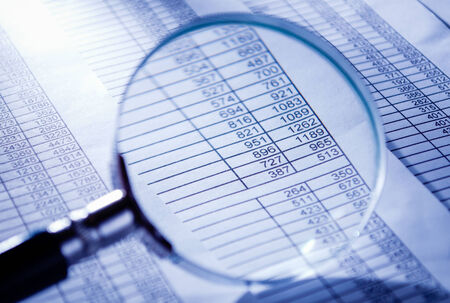 Conceptual Magnifying Glass on Top of Sales Invoice Reports, Emphasizing Scrutinizing Figures. Stock Photo - 34864513