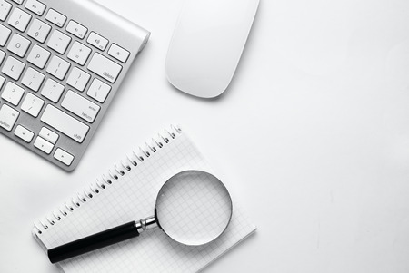 Conceptual image depicting conducting an online search for information with a magnifying glass on a blank notebook alongside a wireless computer mouse and keyboard