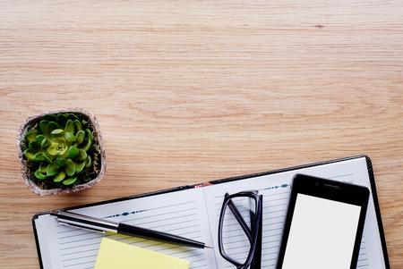 emphasizing: Flower pot, glasses, pen, notebook emphasizing copy space on the tablet screen on light brown desktop