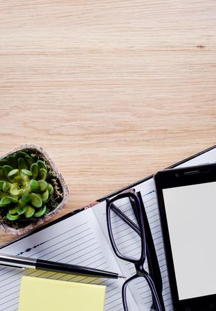 emphasising: Vaso per fiori, occhiali, penna, quaderno sottolineando copia spazio sullo schermo del tablet sulla luce scrivania marrone