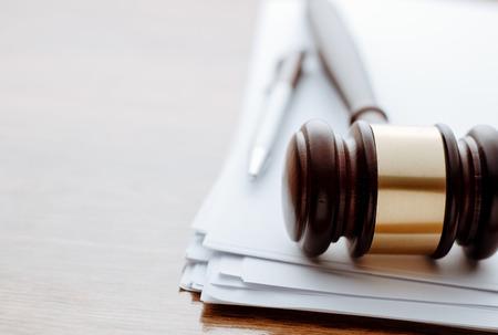 Gavel, Kugelschreiber und Papier für Notizen liegen auf dem Schreibtisch aus Holz. Lizenzfreie Bilder