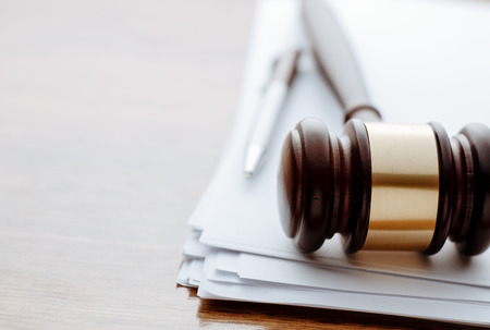 Gavel, ball pen and paper for notes lie on the wooden desk.