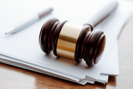 auction: Gavel, ball pen and paper for notes lie on the wooden desk.
