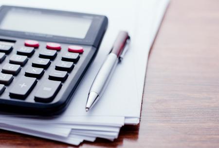 계산기, 펜, 흰 종이 노트에 대 한 나무 테이블의 표면에 거짓말