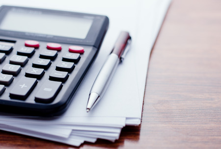 Calculator, pen, white paper for notes lie on the surface of a wooden table Banque d'images