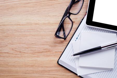 paper and pen: Glasses, pen, cell phone,notebook lie on light brown desktop