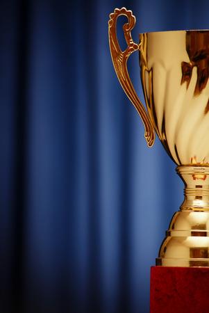 Golden glowing trophy cup on a dark blue background Standard-Bild