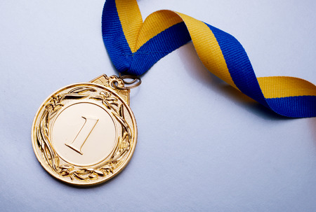 Gold medal in the foreground on yellow blue ribbon