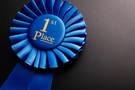 Blue first place winner of the socket with a pleated ribbon on a dark background Standard-Bild