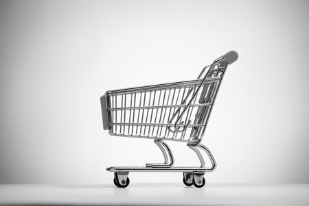 grocery shopping cart: Empty shopping cart, isolated on light background.