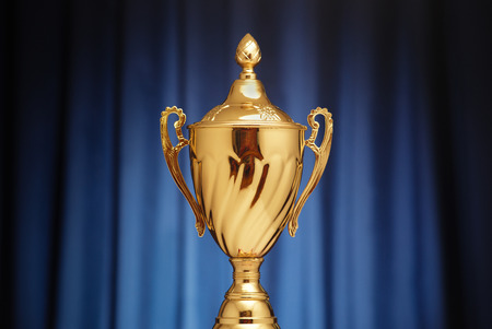first place: Golden glowing trophy cup on a dark blue background Stock Photo
