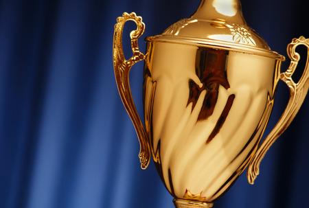 Golden gloeiende trofee kop op een donkere blauwe achtergrond
