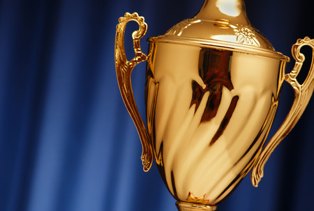 Golden glowing trophy cup on a dark blue background Foto de archivo