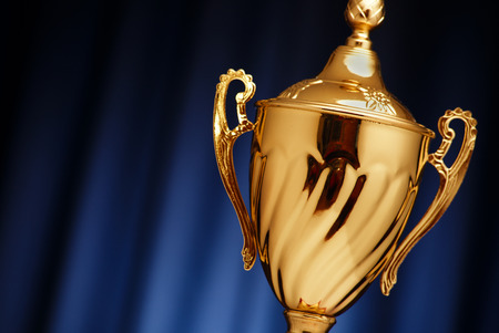 Golden glowing trophy cup on a dark blue background Banque d'images