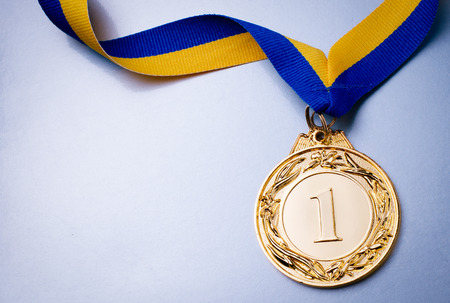Zlatá medaile v popředí na žlutém modrou stuhou