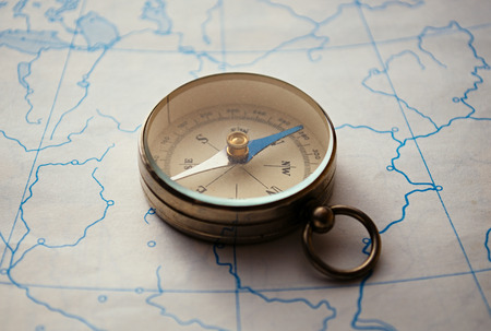 magnetic north: Closeup view of a portable magnetic compass lying on a map