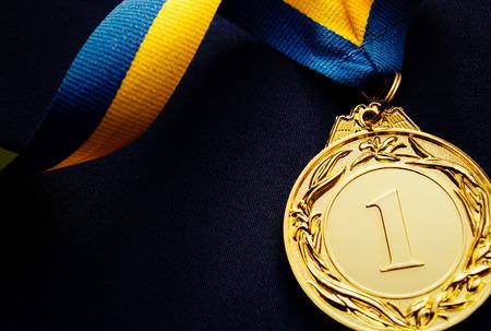 Médaille d'or au premier plan sur un ruban bleu jaune