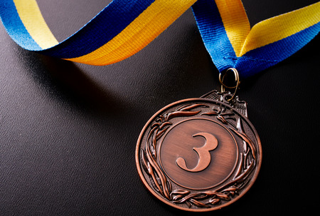 Bronze medal in the foreground on yellow blue ribbon