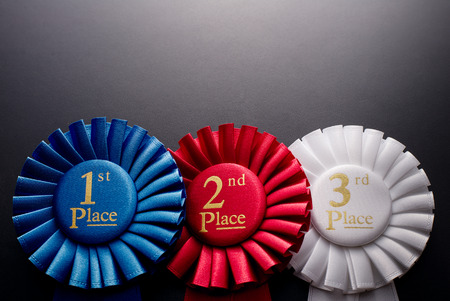 1st, 2nd and 3rd place pleated ribbon rosette on a dark background Stock Photo