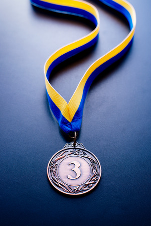 bronze medal: Bronze medal in the foreground on yellow blue ribbon