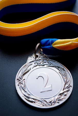 silver medal: Silver medal in the foreground on yellow blue ribbon Stock Photo