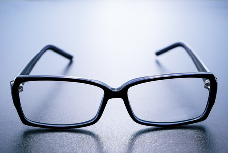 black rimmed: Horn-rimmed glasses with reflection on blue background Stock Photo