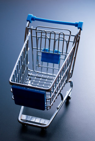 empty shopping cart: Empty shopping cart, isolated on dark blue background.