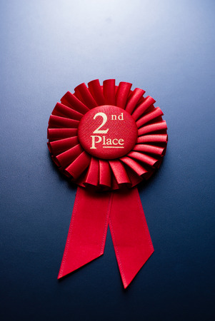 plisse: Red second place winner of the socket with a pleated ribbon on a dark background Archivio Fotografico