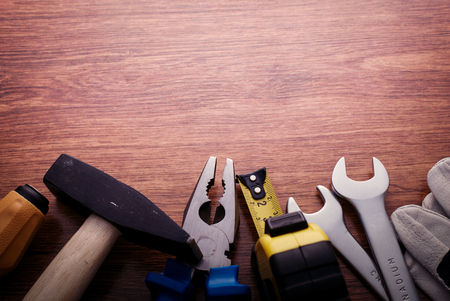 positioned: Close up Hand Work Tools on a Wooden Table, Positioned at the Bottom Border Frame Emphasizing Copy Space Above.