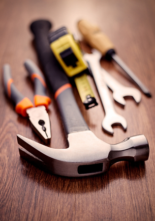 close up   head: Close up Head of a Claw Hammer Hand Tool on Top of a Wooden Table with Other Hand Tools on the Sides