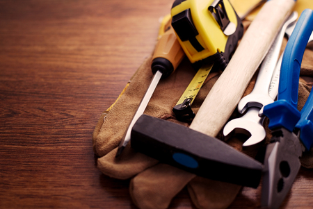 close up  wrench: Close up Hand Tools on a Table with Copy Space on the Left Side, Emphasizing Screw Driver, Measuring Tape, Cross Pein Sledge Hammer, Wrench and Pliers on Top of Hand Gloves Stock Photo