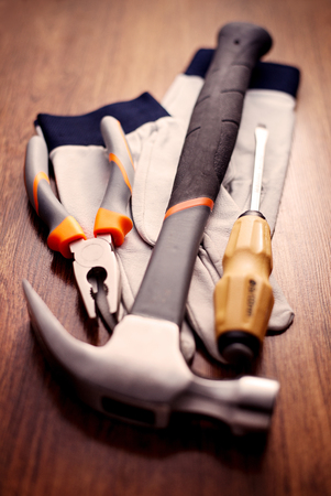 close up  wrench: Close up Claw Hammer, Pliers, Screw Drivers and Hand Gloves on Top of a Wooden Table Stock Photo
