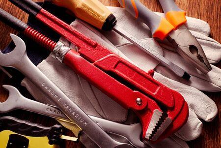 screw driver: Close up Work Tools like Wrenches, Screw Driver and Pliers on Hand Gloves Placed on Top of a Wooden Table