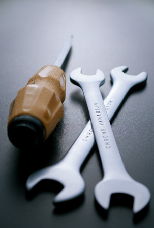close up  wrench: Close up Screw Driver and Open Ended Wrenches Hand Tools on a Gray Background