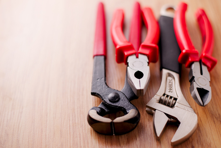 close up  wrench: Closeup adjustable wrench, pliers, claw hammer and pliers on the wooden background