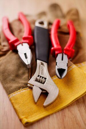alicates: Llave ajustable, alicates y cortador de alambre en la parte superior de los guantes de protección sobre un fondo de madera Foto de archivo