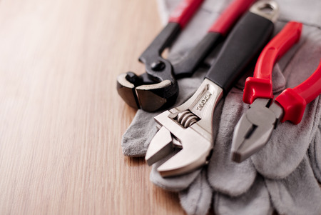 Adjustable wrench, pliers and nail puller on top of the protective gloves on a wooden background photo