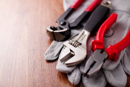 metal fastener: Adjustable wrench, pliers and nail puller on top of the protective gloves on a wooden background Stock Photo