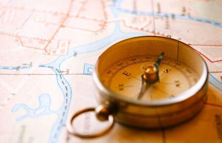 conceptual map: Colgante conceptual de la vendimia con la br�jula para navegar Direcci�n miente encima de un mapa, capturados en el Cierre. Foto de archivo