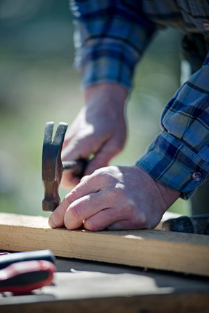 Hands of a man hammering nails into board on natural background