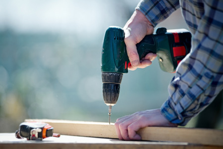 Hands of a man carpenter builder working with a electric screwdriver with a blurred background Stock Photo - 38737404