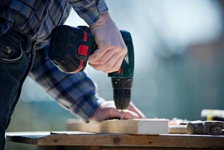Mains d'un constructeur de l'homme de charpentier travaillant avec un tournevis électrique avec un fond flou