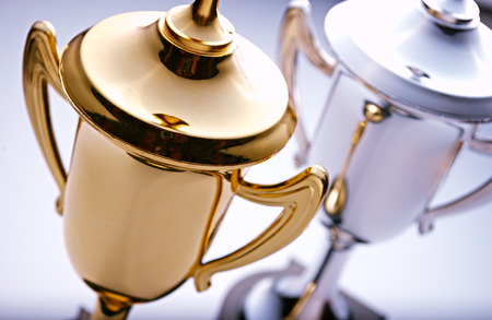 El oro y trofeos de plata en espera de ser adjudicado al ganador y finalista en un concurso con el foco de la copa de oro delante Foto de archivo - 38737527